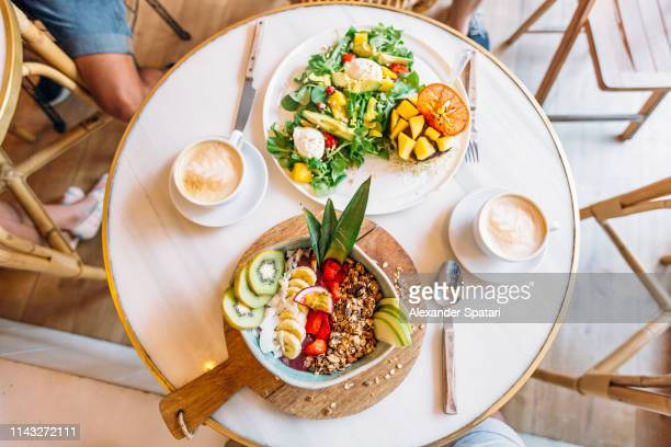 healthy breakfast with acai smoothie bowl and mango salad, directly above view - acai stock pictures, royalty-free photos & images
