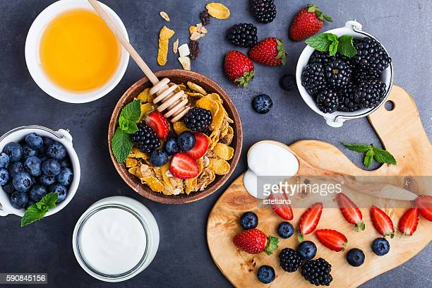 Healthy breakfast with cereal, fresh berries, yogurt and honey over gray table viewed from above
