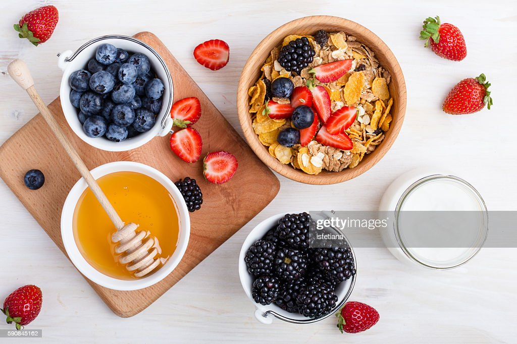 Healthy breakfast with cereal, fresh berries, yogurt and honey over white rustic wooden table viewed from above : Stock Photo
