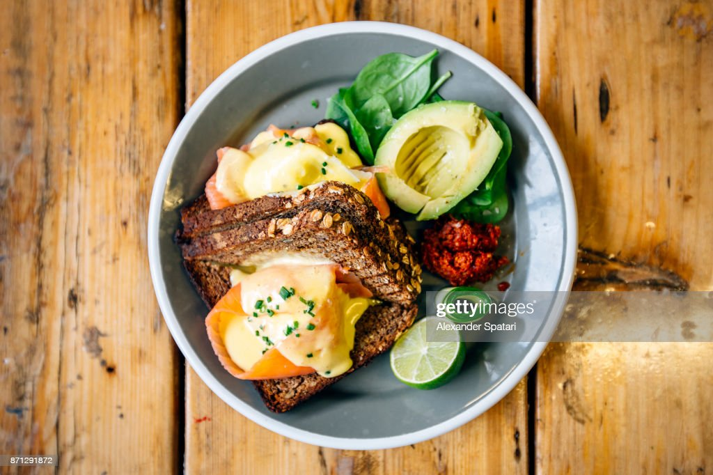 Healthy breakfast with rye bread, salmon, poached egg, avocado and lime : Stock Photo