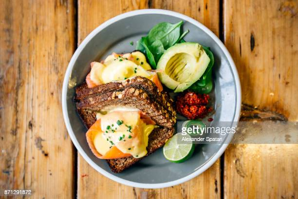 healthy breakfast with rye bread, salmon, poached egg, avocado and lime - the brunch stock pictures, royalty-free photos & images