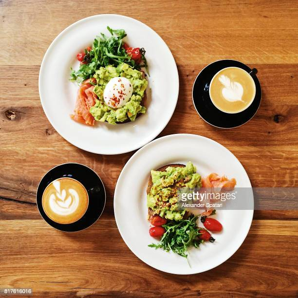 Healthy brunch with avocado and poached egg on toast, high angle view