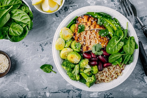 Healthy buddha bowl lunch with grilled chicken, quinoa, spinach, avocado, brussels sprouts, broccoli, red beans with sesame seeds 920931456
