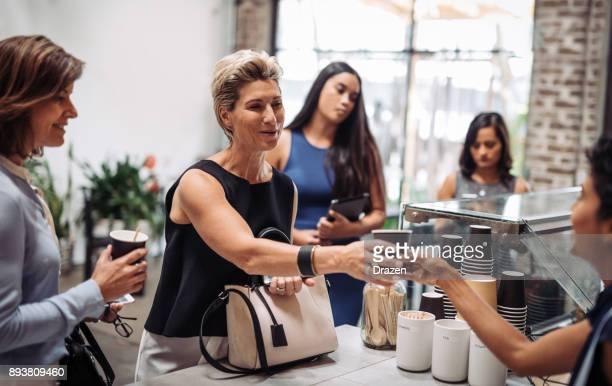 Healthy businesswoman ordering organic coffee in vegan snack bar