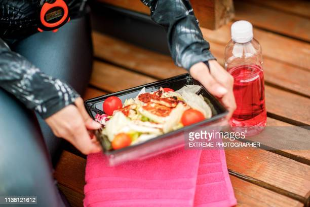 a healthy colorful salad with pieces of grilled chicken and cherry tomato in a take-out plastic box, ready to eat - plastic plate stock photos and pictures
