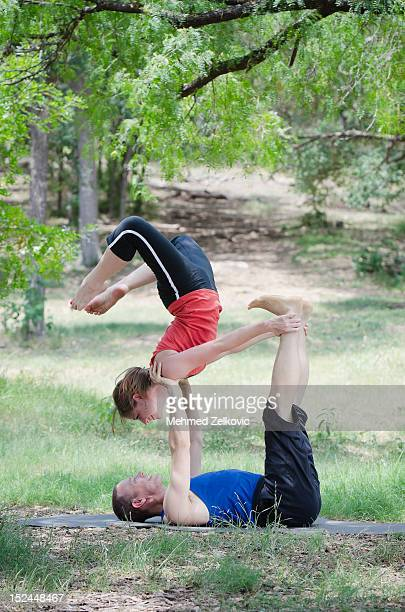 Healthy couple doing acro yoga in nature