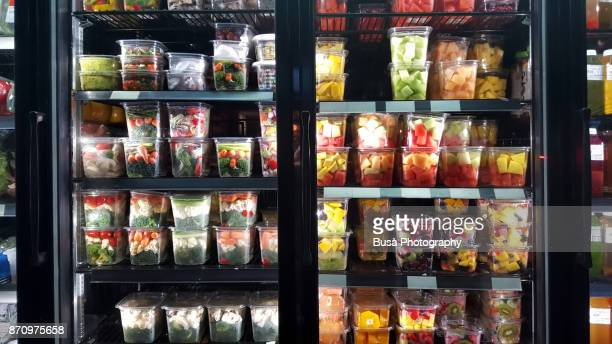Healthy cut fruit and vegetables on display in store window of a grocery store in the East Village, New York City