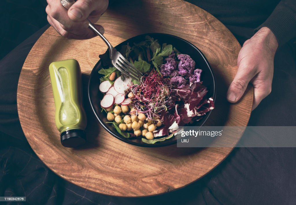 Healthy dinner, lunch in the sofa. Man  eating vegan championship game or Buddha bowl with vegetables, fresh salad, chickpeas, soybean sprouts, purple broccoli : Stock Photo