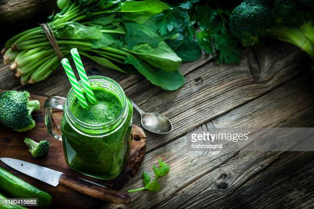 healthy drink: green vegetables juice on rustic wooden table with copy space - detox stock pictures, royalty-free photos & images