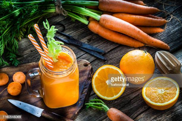 healthy drink: orange and carrot juice on rustic wooden table - orange stock pictures, royalty-free photos & images