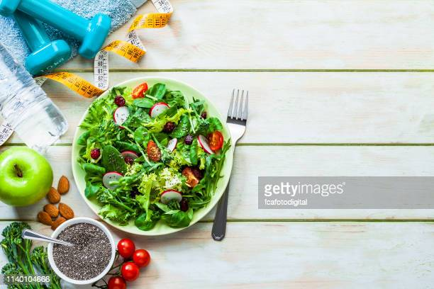 healthy eating and exercising backgrounds: fresh healthy salad, dumbbells and tape measure with copy space - alimentação saudável imagens e fotografias de stock