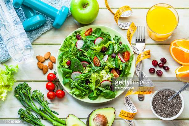 healthy eating and exercising concepts: fresh healthy salad, dumbbells and tape measure - squash sport stock pictures, royalty-free photos & images