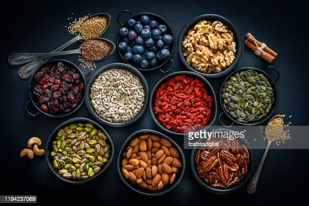 healthy eating: assortment of nuts, seeds and fruits. top view. - antioxidant stock pictures, royalty-free photos & images