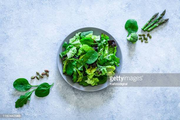 healthy eating: fresh green salad shot from above on gray background - green salad stock pictures, royalty-free photos & images