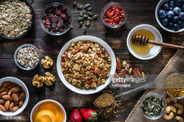 healthy eating: homemade granola preparation ingredients. top view. - granola stock pictures, royalty-free photos & images