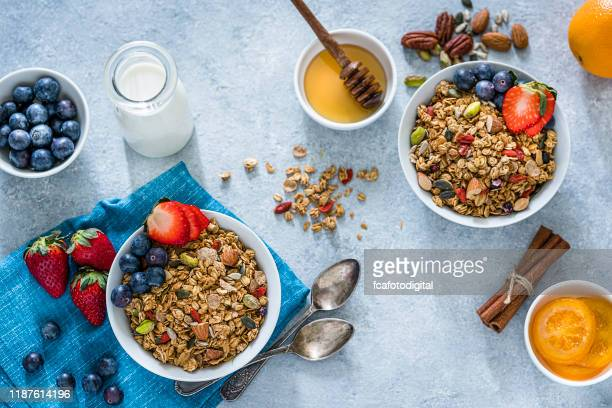 healthy eating: two granola bowls with fruits for breakfast. top view - granola stock pictures, royalty-free photos & images
