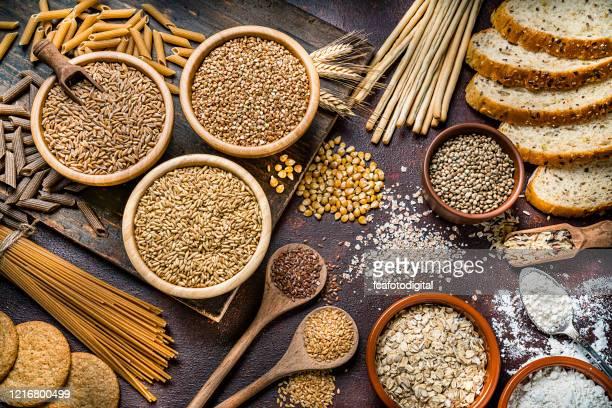 alimentazione sana: cibo integrale natura morta girata su un tavolo di legno rustico - cereale foto e immagini stock