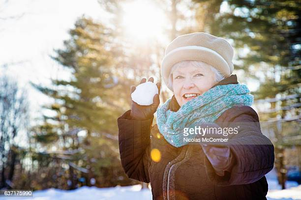Healthy energetic senior woman throwing snow ball