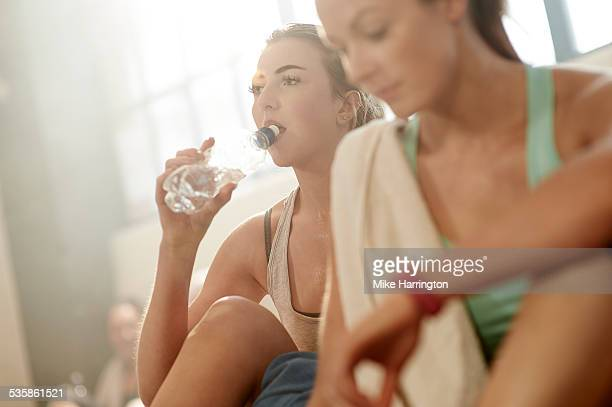 Healthy female drinking water after gym workout