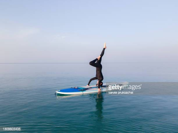 healthy female exercising yoga together poses with sub board or stand up paddle board . - awe stock pictures, royalty-free photos & images