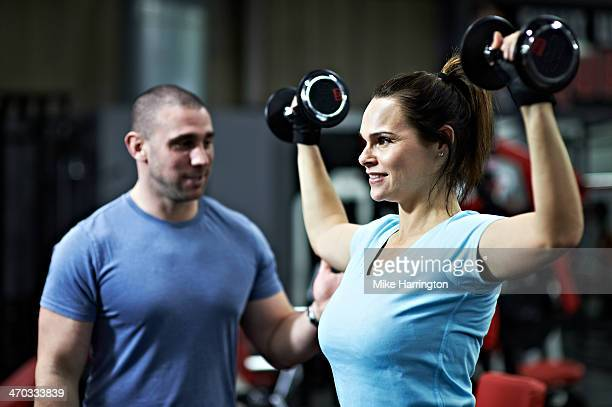 Healthy Female Lifting Dumbbells Above Head in Gym