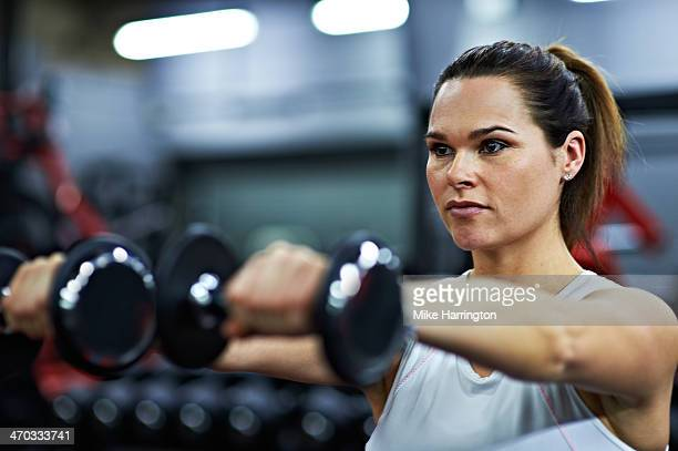 Healthy Female Lifting Free Weights in Gym