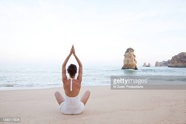 healthy female meditating along coastlin - neckline stock pictures, royalty-free photos & images