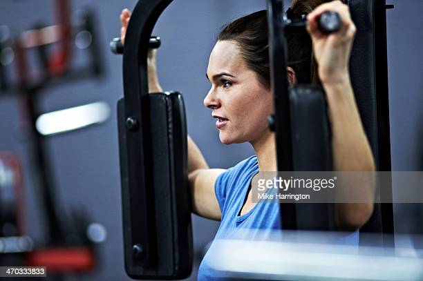 Healthy Female Using Pectoral Fly Machine in Gym