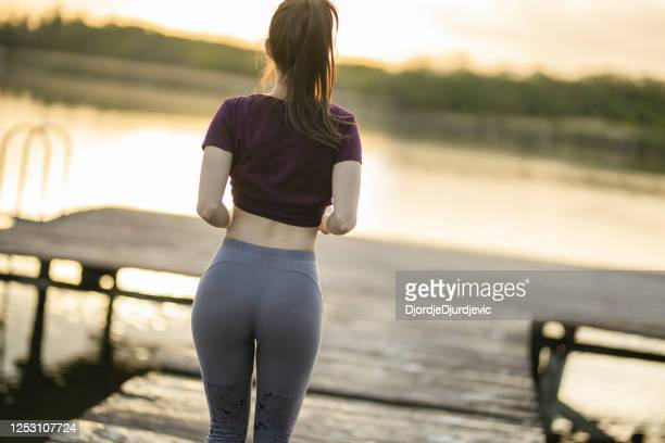 healthy fitness woman jogging on sunset near lake - beautiful bums stock pictures, royalty-free photos & images