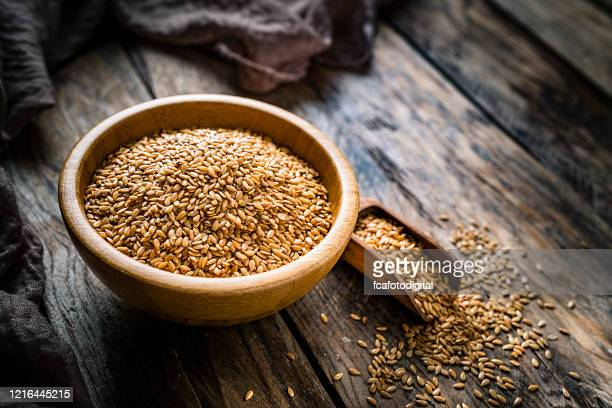 healthy food: flax seeds in a bowl shot on rustic wooden table - flax seed stock pictures, royalty-free photos & images