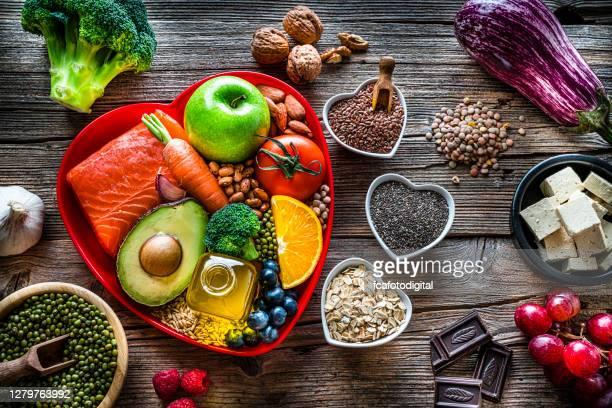 cibo sano per abbassare il colesterolo e la cura del cuore girato sul tavolo di legno - alimentazione sana foto e immagini stock