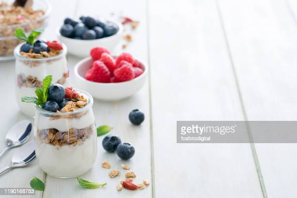 healthy food: homemade yogurt with granola on breakfast table. copy space - yoghurt stock pictures, royalty-free photos & images