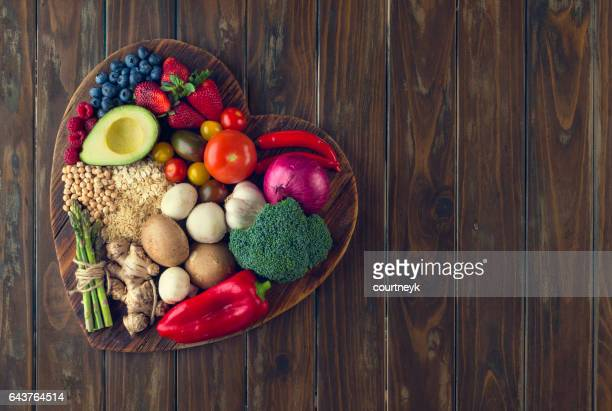 healthy food on a heart shape cutting board - healthy lifestyle stock pictures, royalty-free photos & images