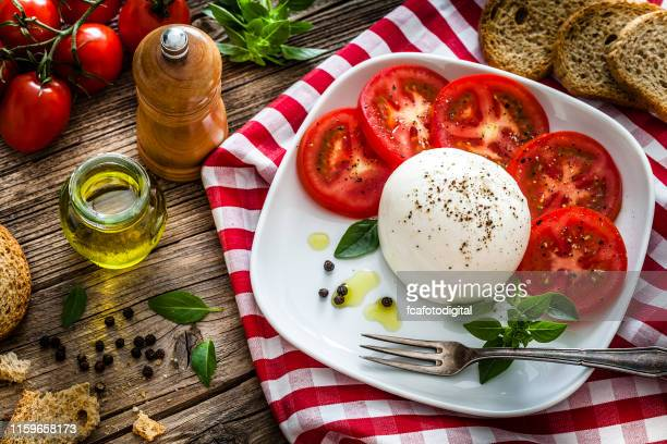 healthy fresh burrata cheese salad on rustic wooden table - italian food stock pictures, royalty-free photos & images