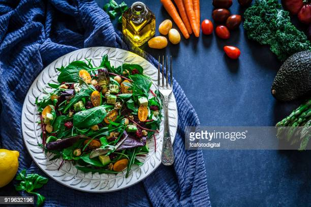 Healthy fresh salad plate on bluish tint table