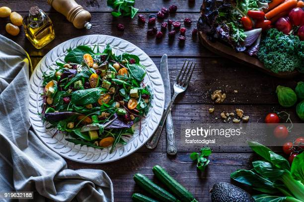 Healthy fresh salad plate on rustic wooden table