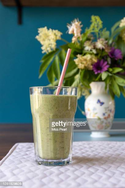 healthy green smoothie drink with pink paper straw - kildare stock pictures, royalty-free photos & images