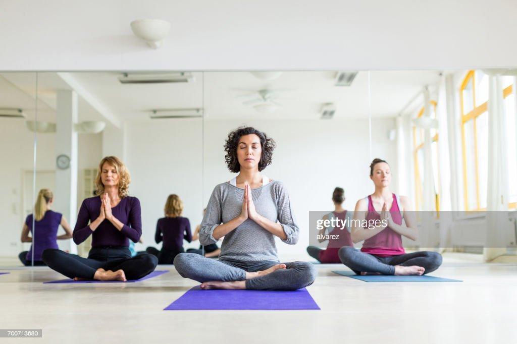 Gesunde Gruppe von Frauen, die Meditation in Yoga-Pose im Fitness-Studio : Stock-Foto