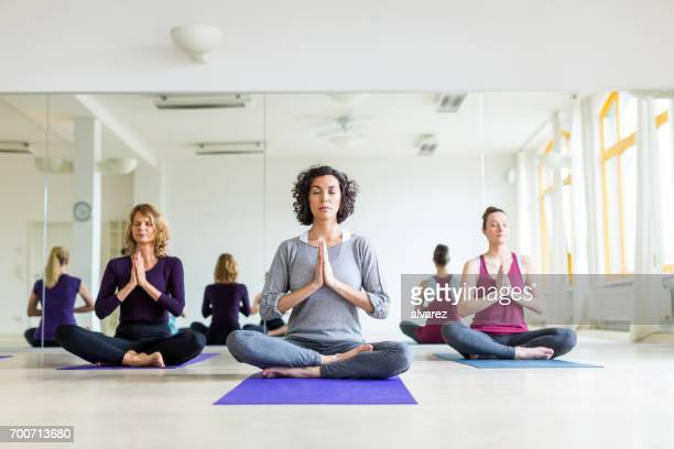 Healthy group of females meditating in yoga pose in gym