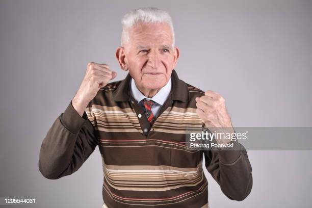 healthy , happy senior man punching on studio background - human body part stock-fotos und bilder
