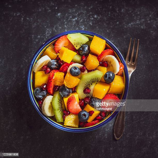 healthy homemade fruit salad bowl shot from above. - ripe stock pictures, royalty-free photos & images