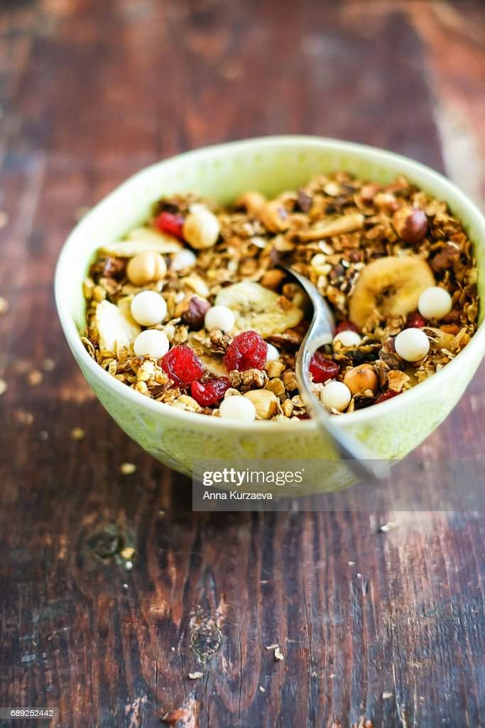 Healthy homemade granola or muesli with toasted oats, dried cherry, cranberry, figs, raisin, hazelnuts, cashew, walnuts, white chocolate chips in a bowl for breakfast or snack, selective focus : Stock Photo