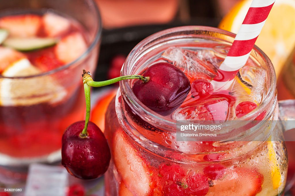 Healthy infused detox water with fresh berries and fruits in mason jar : Stock Photo