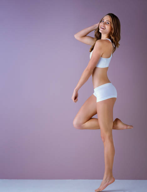 Studio shot of a healthy young woman posing against a purple background