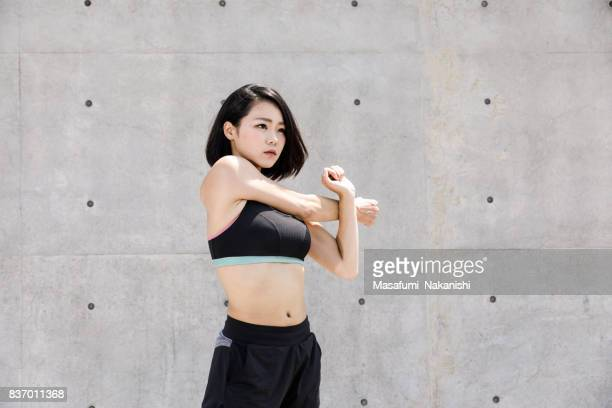 healthy japanese woman is stretching outdoors - tank top stock photos and pictures