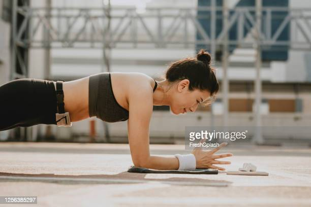 healthy lifestyle: a sporty asian woman doing a plank while following an online workout session on her mobile phone - plank position stock pictures, royalty-free photos & images