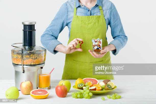 Healthy lifestyle and diet concept. Fruit juice, pills and vitamin supplements, woman making a...