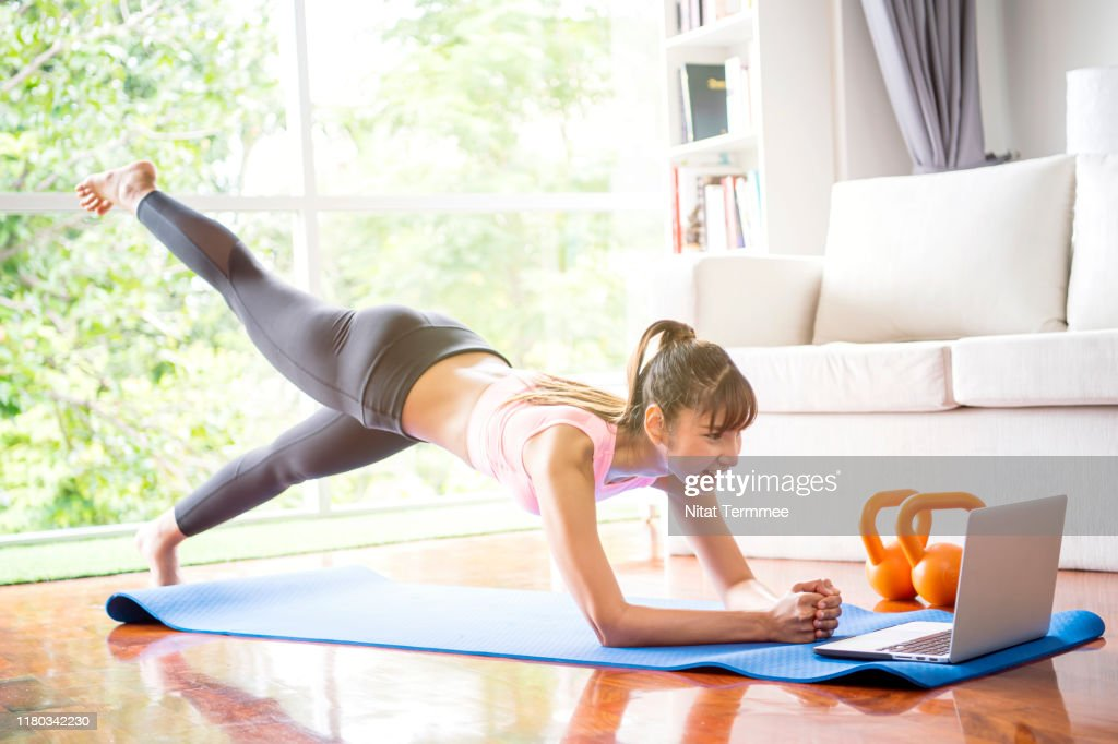 Healthy lifestyle and work life balance concepts. Young woman doing yoga excercise with online app on computer laptopn in her living room at home. : Stock Photo