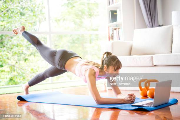 healthy lifestyle and work life balance concepts. young woman doing yoga excercise with online app on computer laptopn in her living room at home. - リラクゼーション体操 ストックフォトと画像