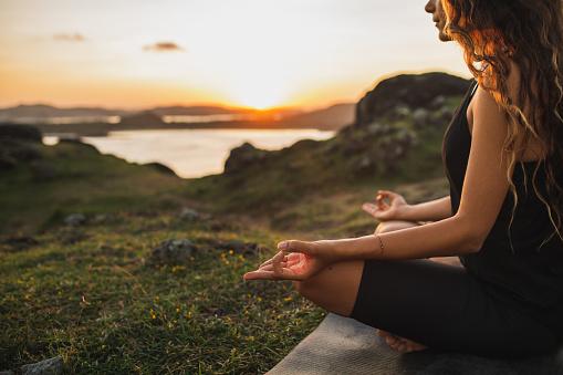 Healthy Lifestyle and Yoga Concept. Close-up hands. Woman do yoga outdoors at sunrise in lotus position. Woman exercising and meditating in morning. Nature background. 1159495308